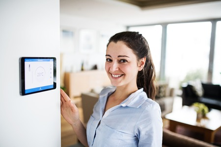 A woman looking at tablet with smart home screen.