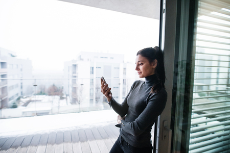 Woman by the window holding smartphone.