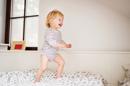 Cute toddler boy jumping on the bed. Stock Photo