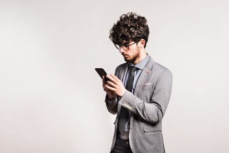 Portrait of a young man with smartphone in a studio.