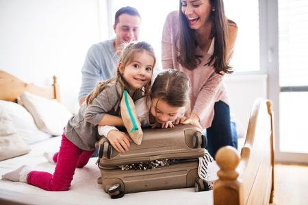 Familia joven con dos hijos de embalaje para vacaciones. Foto de archivo