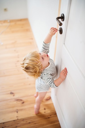 Toddler child in a dangerous situation at home. Banco de Imagens - 99980610