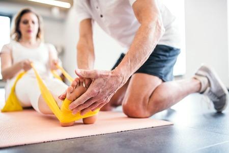 Fisioterapista senior irriconoscibile che lavora con un paziente di sesso femminile.