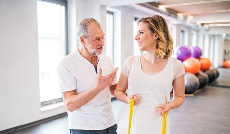 Senior male physiotherapist working with a female patient. Stock Photo