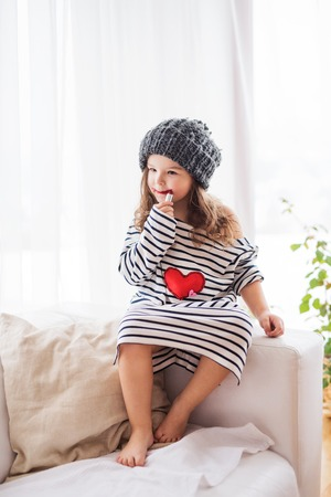 A small happy girl in striped T-shirt at home applying a lipstick. Stock Photo