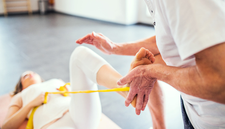 Unrecognizable senior physiotherapist working with a female patient. Stock Photo