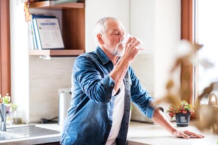 Senior man drinkwater in de keuken.