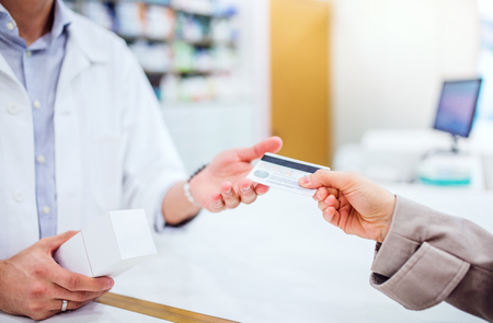 Unrecognizable customer giving a credit card to a male pharmacist. Standard-Bild