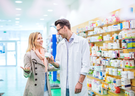 Male pharmacist serving a female customer.