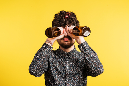 Studio portrait of a young man holding bottles on a yellow background. Фото со стока