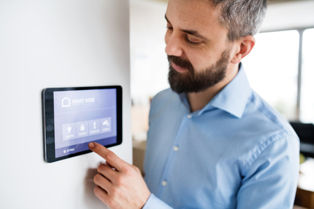 A man pointing to a tablet with smart home screen at home. Archivio Fotografico