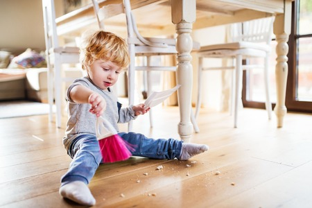 A toddler boy with brush and dustpan at home.