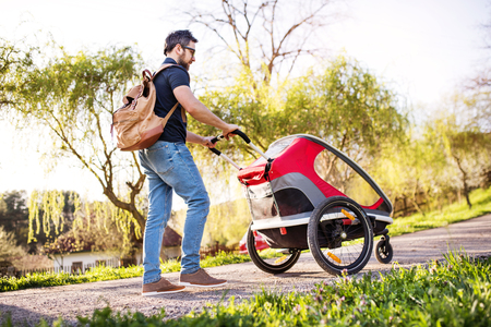 A father with jogging stroller on a walk outside in spring nature.