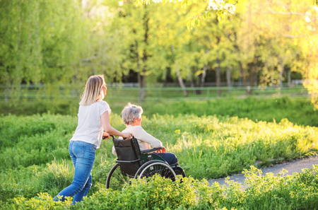 Elderly grandmother in wheelchair with granddaughter in spring nature. 스톡 콘텐츠 - 100624578