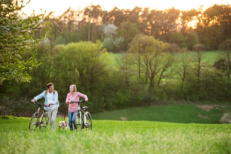 Beautiful senior couple with bicycles and dog outside in spring nature. Фото со стока