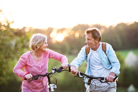 Beautiful senior couple with bicycles outside in spring nature. Foto de archivo
