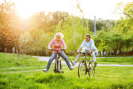Beautiful senior couple with bicycles outside in spring nature. 免版税图像