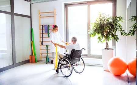 Young woman physiotherapist working with a senior man in wheelchair. Stock Photo