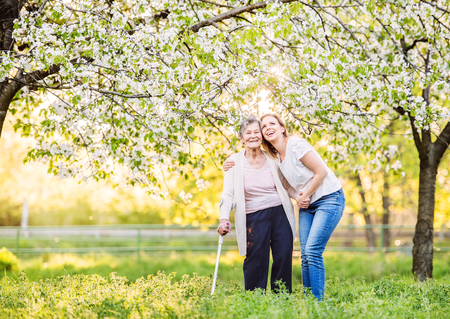 Elderly grandmother with crutch and granddaughter in spring nature. Banque d'images - 100971113