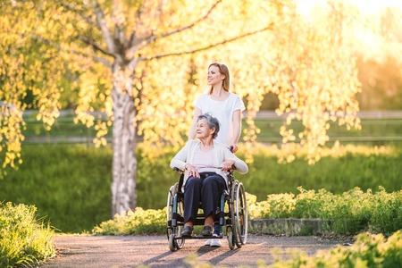 Abuela anciana en silla de ruedas con nieta en la naturaleza de primavera.
