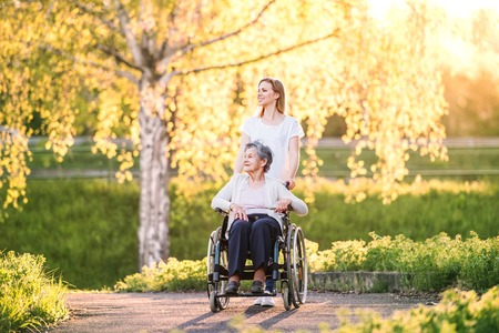 Elderly grandmother in wheelchair with granddaughter in spring nature. Stock Photo