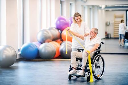 Fisioterapista della giovane donna che lavora con un uomo anziano in sedia a rotelle.