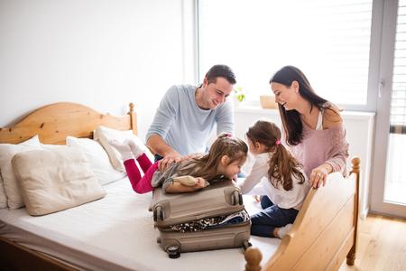 Junge Familie mit zwei Kindern, die für Urlaub packen.