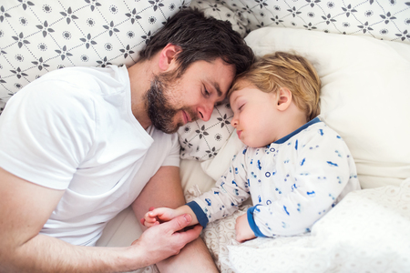 Father holding hand of a sleeping toddler boy in bed at home.
