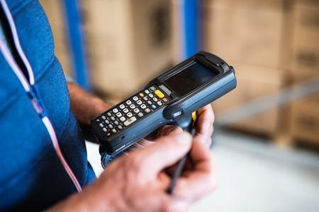 Mannelijke magazijnmedewerker met barcodescanner.