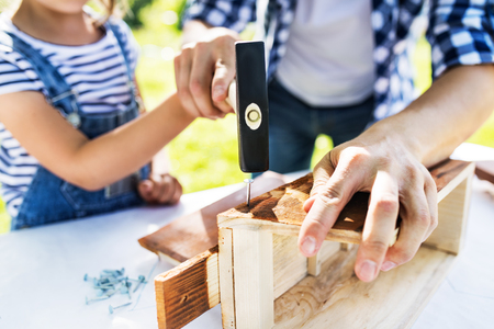 Father with a small daughter outside, making wooden birdhouse. Stock Photo
