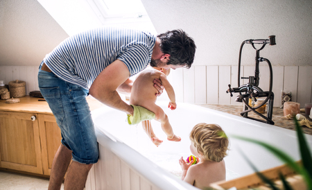 Father washing two toddlers in the bathroom at home. Banco de Imagens - 101684170