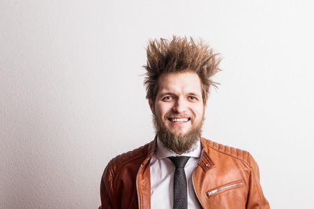 Portrait of a young hipster man with messy hairstyle in a studio. Copy space.