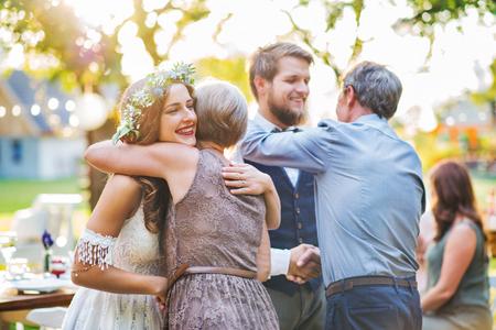 Invitados felicitando a la novia y el novio en la recepción de la boda al aire libre en el patio trasero. Foto de archivo