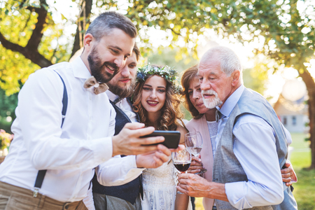 Bride, groom and guests with smartphones taking selfie outside at wedding reception. Archivio Fotografico - 101886946