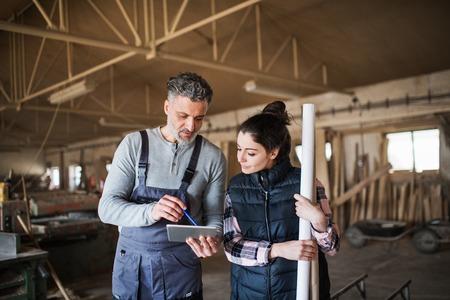 hombre y mujer trabajadores con tableta en el taller de carpintería