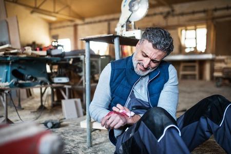 Homme avec une main blessée après un accident du travail dans l'atelier de menuiserie.