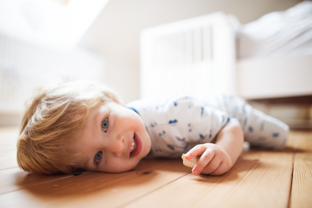 A toddler boy on the floor in the bedroom at home. Stock Photo