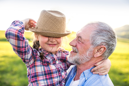 A small girl with grandfather outside in spring nature, having fun. Stock Photo