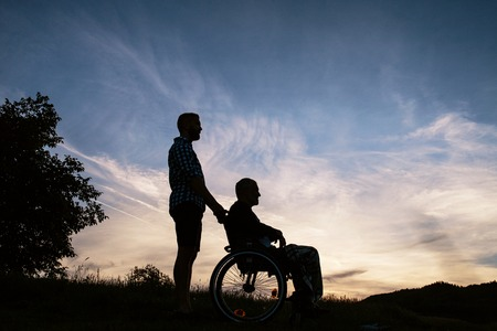 A silhouette portrait of adult son with senior father in wheelchair in nature at sunset.
