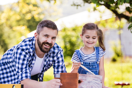 Father with a small daughter outside, painting wooden birdhouse. Reklamní fotografie