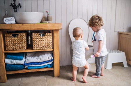 Two toddler children with toothbrush standing by the toilet in the bathroom at home. Stockfoto