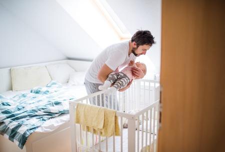 Père mettant une petite fille endormie dans un lit bébé à la maison.