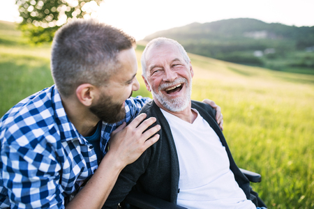 An adult hipster son with senior father in wheelchair on a walk in nature at sunset, laughing. Foto de archivo
