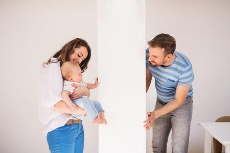 Young family with a baby boy at home, having fun.