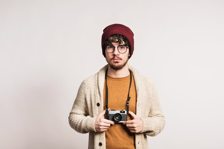 Portrait of a young man with camera in a studio.