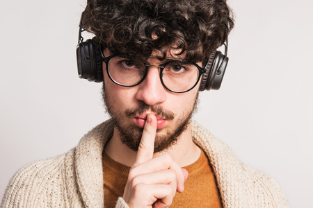 Portrait of a young man with headphones in a studio, finger on his mouth.