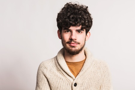 Portrait of a young man in woollen cardigan in a studio. Copy space. Stockfoto - 102679228