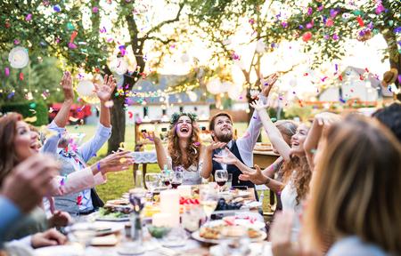 Bruid en bruidegom met gasten bij huwelijksreceptie buiten in de achtertuin.