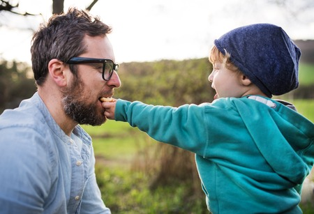 A toddler boy giving his father a biscuit outside in spring nature.