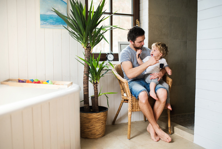Father and a toddler boy sitting on a chair and brushing their teeth at home. Stok Fotoğraf
